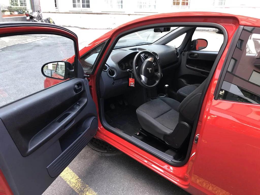 Mitsubishi Colt von Innen fotografiert mit offener Türe und Lenkrad im Blick